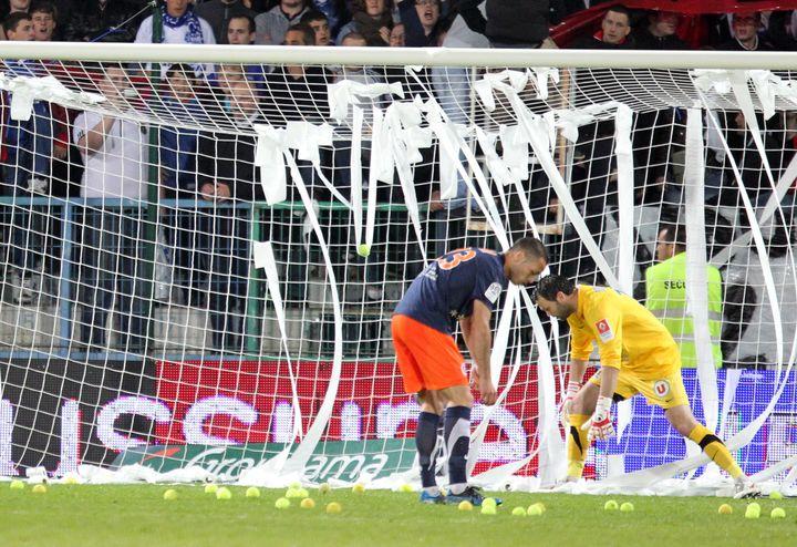 Les joueurs de Montpellier ramassent des balles de tennis jetées sur le terrain par des supporters d'Auxerre, en signe de mécontentement. (JEAN BAPTISTE QUENTIN / MAXPPP)