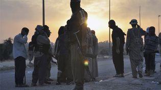 Des combattants de l'Etat islamique en Irak et au Levant montent la garde à un poste de contrôle, le 11 juin 2014, à Mossoul (Irak). (REUTERS)