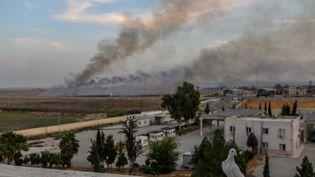 Un panache de fumée s'élève de la ville syrienne deTal Abyad, jeudi 10 octobre 2019, au lendemain du début de l'offensive turque contre les forces kurdes. (BULENT KILIC / AFP)