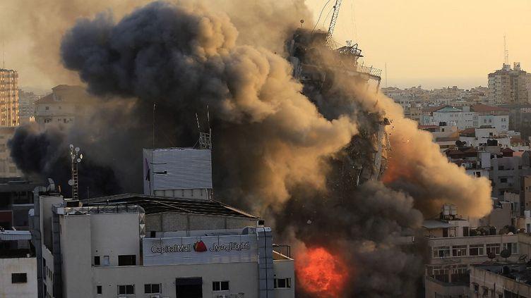 Une tour s'effondre dans la bande de Gaza après des bombardements israéliens, le 12 mai 2021 dans lesTerritoires palestiniens occupés. (QUSAY DAWUD / AFP)