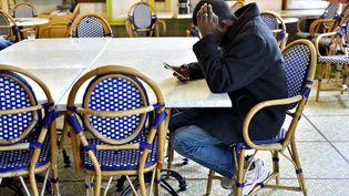 Un homme venu du Soudan consulte son téléphone portable dans un centre d'accueil et d'orientation pour migrants, à Saint-Brévin-les-Pins (Loire-Atlantique), le 4 janvier 2017. (LOIC VENANCE / AFP)