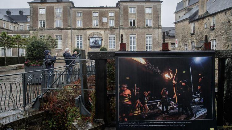 Des passants regardent les clichés de photojournalistes exposés dans la ville de Bayeux (Calvados), à l'occasion du prix des correspondants de guerre, le 5 octobre 2020. (SAMEER AL-DOUMY / AFP)
