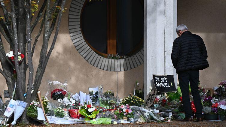 Un homme se recueille devant le collège du Bois d'Aulne à Conflans-Sainte-Honorine (Yvelines), en hommage à Samuel Paty, professeur assassiné, le 19 octobre 2020. (ANNE-CHRISTINE POUJOULAT / AFP)