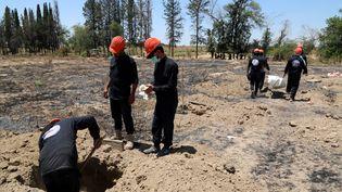 Des enquêteurs fouillent un site près de Raqqa dans le nord-est de la Syrie où près de 200 corps ont été retrouvés (7 juillet 2019). (AHMED MARDNLI / EPA)