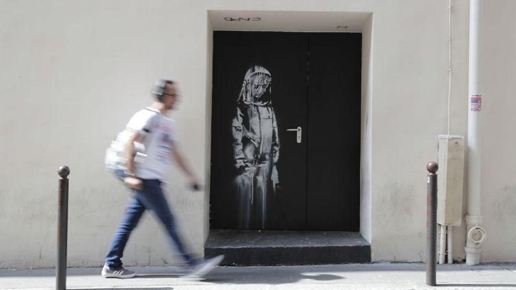 Une œuvre attribuée à l'artiste britannique Banksy sur l'une des issues de secours du Bataclan, le 25 juin 2018 à Paris. (THOMAS SAMSON / AFP)