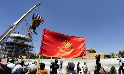 Mise en place, dans le centre de Skopje le 21 juin 2011, d'une statue d'Alexandre le Grand sur son cheval Bucéphale. Des Macédoniens slaves brandissent un fanion avec le soleil de Vergina, symbole de l'indépendance de leur pays.Vergina Sun fla