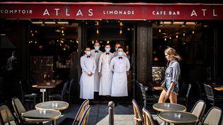 Des serveurs d'un restaurant parisien devant leur établissement, en juin 2020. (MARTIN BUREAU / AFP)