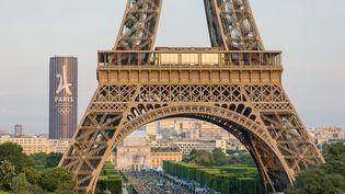La tour Eiffel à Paris, avec la tour Montparnasse au second plan, ornée du logo de candidature de la capitaleen vue d'accueillir les JO 2024. (GARDEL BERTRAND / AFP)