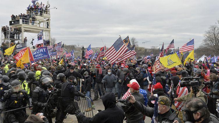 Des participants à l'attaque du Capitole affrontent les forces de sécurité le 6 janvier 2021 à Washington, aux Etats-Unis. (JOSEPH PREZIOSO / AFP)