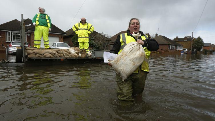 Distribution de sacs de sables pour les résidents deEgham, sous les eaux,le long de la Tamise, el 13 février 2014 (LUKE MACGREGOR / REUTERS )