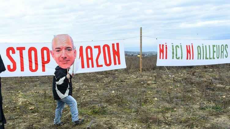 Un membre d'Attac porte une pancarte représentant Jeff Bezos, le fondateur d'Amazon, lors d'une mobilisation contre l'installation d'un entrepôt du géant de la distribution à Fournès (Gard), le 30 janvier 2021. (SYLVAIN THOMAS / AFP)