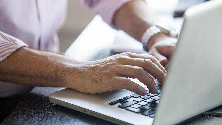 Un homme travaillant sur son ordinateur. Image d'illustration. (MAXPPP)