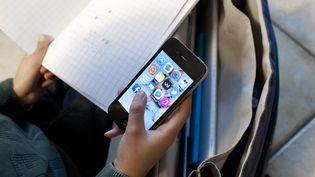 Un élève en train de faire ses devoirs avec un telephone portable a la main. (Photo d'illustration) (SEBASTIEN JARRY / MAXPPP)