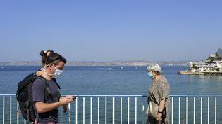 Des passants en front de mer à Marseille, le 14 septembre 2020. (NICOLAS TUCAT / AFP)