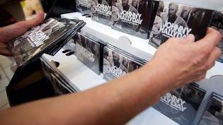Un homme tient des exemplaires du disque posthume de Johnny Hallyday, le 19 octobre 2018, dans un supermarché Auchan à Calais (Pas-de-Calais). (MAXPPP)