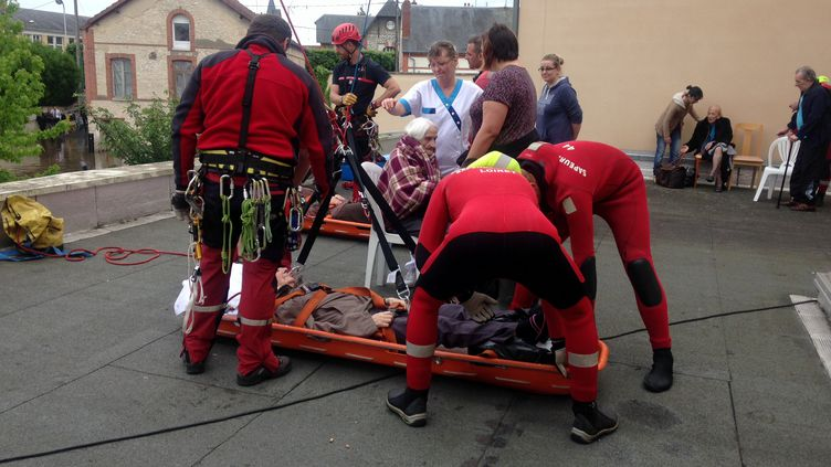 Des secouristes installentune résidente de la maison de retraite de Montargis (Loiret) sur une nacelle. (ELISE LAMBERT / FRANCETV INFO)