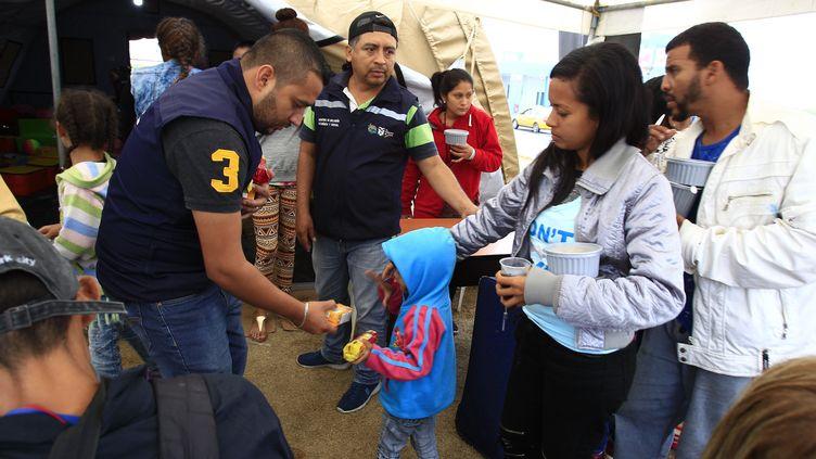 Les migrants venezueliens reçoivent de la nourriture pendant qu'ils attendent à Huaquillas en Équateur de pouvoir passer au Pérou. (JOSE JACOME / EFE)