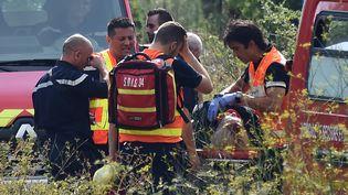 Les secouristes transportent un blessé sur une civière le 17 Août, 2017, suite à un accident de train à Saint-Aunès près de Montpellier (SYLVAIN THOMAS / AFP)