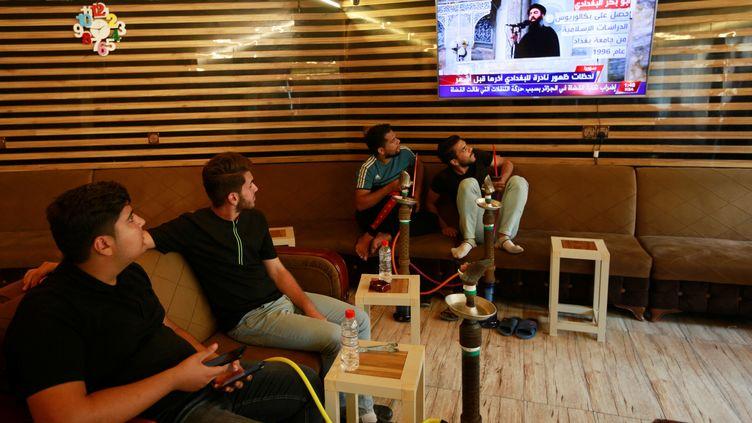 Des Irakiens suivent les informations à la télévision, qui annonce la mort d'Abou Bakr Al-Baghdadi, le 27 octobre 2019, dans un café de Najaf. (ALAA AL-MARJANI / REUTERS)