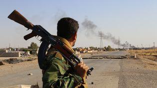 Un peshmerga kurde, observant la ville de Celavle (Irak), en passe d'être reprise aux combattants de l'Etat islamique, le 24 août 2014. (FERIQ FEREC / ANADOLU AGENCY / AFP)