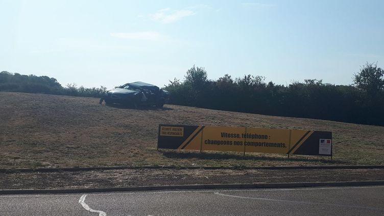 Une carcasse de voiture accidentée, installée sur un rond-point de VIllefargeau, entre Auxerre et Toucy (Yonne), le 1er août. (MAUREEN SUIGNARD / RADIO FRANCE)