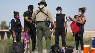 Des migrants guatémaltèques à la frontière entre les Etats-Unis et le Mexique, à Yuma, dans l'Arizona (Etats-Unis), le 12 mai 2021. (RINGO CHIU / AFP)