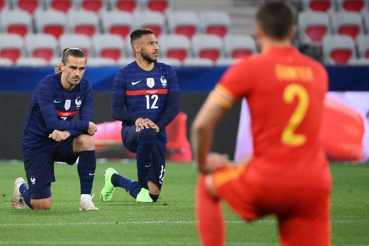 Les joueurs français Antoine Griezmann et Corentin Tolisso, genoux à terre pour montrer leur soutien au mouvement antiraciste, contre le pays de Galles, le 2 juin 2021, à Nice. (FRANCK FIFE / AFP)