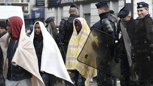 Des policiers encadrent des migrants au cours de l'évacuation du campement de Stalingrad, vendredi 4 novembre 2016 à Paris. (PHILIPPE LOPEZ / AFP)