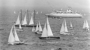 Les concurrents de la première Route du Rhum au départ de Saint-Malo, suivis notamment par le ferry affrété par les organisateurs, le4 novembre 1978. (JEAN-PIERRE PREVEL / AFP)
