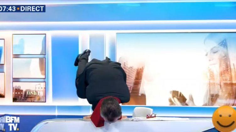 Capture d'écran de BFMTV montrant Christophe Barbier réalisant le poirier en direct, sur le plateau de la chaîne, le 3 janvier 2018. (BFMTV)