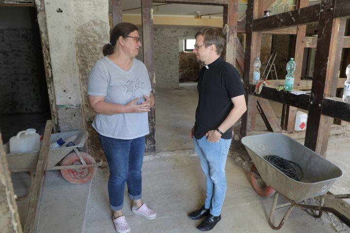 Le prêtre Heiko Marquardsen discute avec une habitante d'Ahrweiler (Allemagne) touchée par les inondations, le 25 août 2021. (VALENTINE PASQUESOONE / FRANCEINFO)