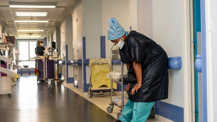 Une soignante épuisée dans une aile éphémère de patients Covid à l'hôpital Saint-Camille de Bry-sur-Marne (Val-de-Marne), le 16 octobre 2020. (ALINE MORCILLO / HANS LUCAS / AFP)