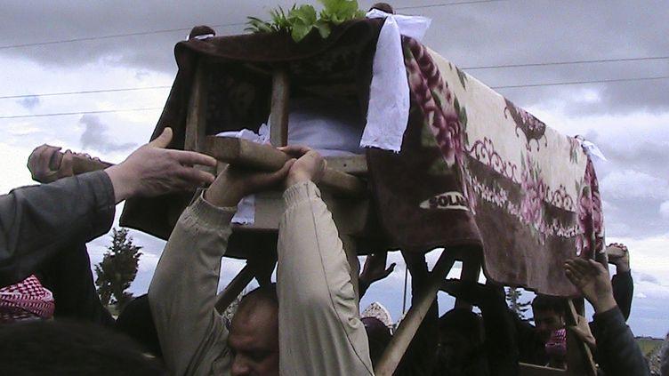 Des habitants de Maarat Al-Masrin, dans la province d'Idleb (Syrie), enterrent une victime des bombardements, le 14 mars 2012. (REUTERS)