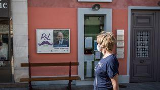 Une femme passe devant une affiche du maire de Sceaux, dans les rues de cette ville des Hauts-de-Seine, le 7 avril 2020. (CHRISTOPHE PETIT TESSON / EPA / AFP)
