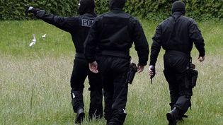 Des policiers du Raid patrouillent le 13 mai 2014 dans une cité de la banlieue de Strasbourg lors d'une opération antiterroriste. (FREDERICK FLORIN / AFP)