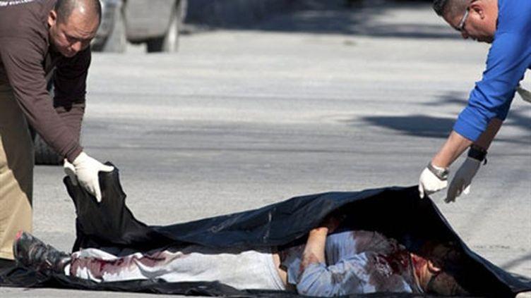 Des policiers recouvrent un homme tué par des trafiquants de drogue, à Ciudad Juarez, le 12 janvier 2010 (AFP PHOTO/Jesus Alcazar)