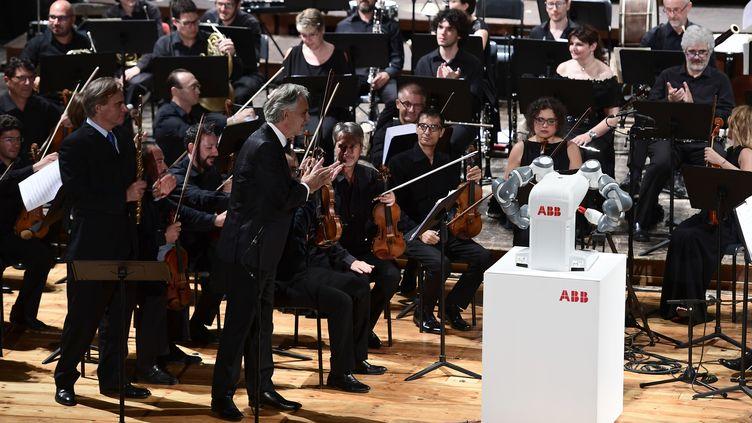 Le robot humanoïde Yumi dirige le ténor Andrea Bocelli (au centre) et l'orchestre philharmonique de Lucques, le 12 septembre 2017 à Pise (Italie). (MIGUEL MEDINA / AFP)