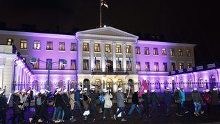 Le couple présidentiel salue des étudiants finlandais qui défilent devant le palais pour célébrrer les 100 ans de l'indépendance, à Helsinki (Finlande). (RONI REKOMAA / LEHTIKUVA)