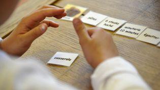 """Un enfant autiste travaille avec une éducatrice, le 24 avril 2008 à Paris à l'institut médico-éducatif """"Les petites victoires"""". (FRANCK FIFE / AFP)"""
