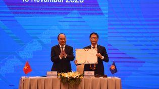 Le Premier ministre vietnamien Nguyen Xuan Phucet son ministre de l'Industrie et du Commerce Tran Tuan Anh, lors de la cérémonie de signature du Partenariat économique régional global (RCEP) au sommet de l'Asean,à Hanoi le 15 novembre 2020. (NHAC NGUYEN / AFP)