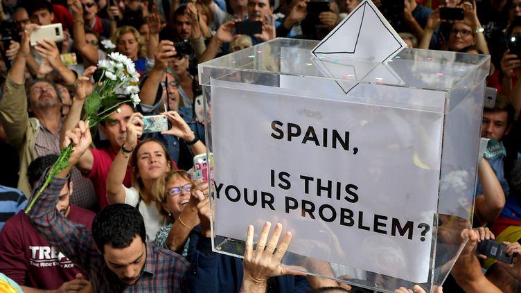 Des manifestants brandissent une urne symbolique, lors d'une manifestationen faveur de l'indépendance devant le siège du gouvernement régional de Catalogne,à Barcelone (Espagne), le 20 septembre 2017. (LLUIS GENE / AFP)