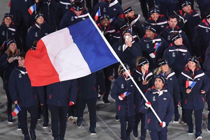 Martin Fourcade défile avec le drapeau français (FRANCK FIFE / POOL)