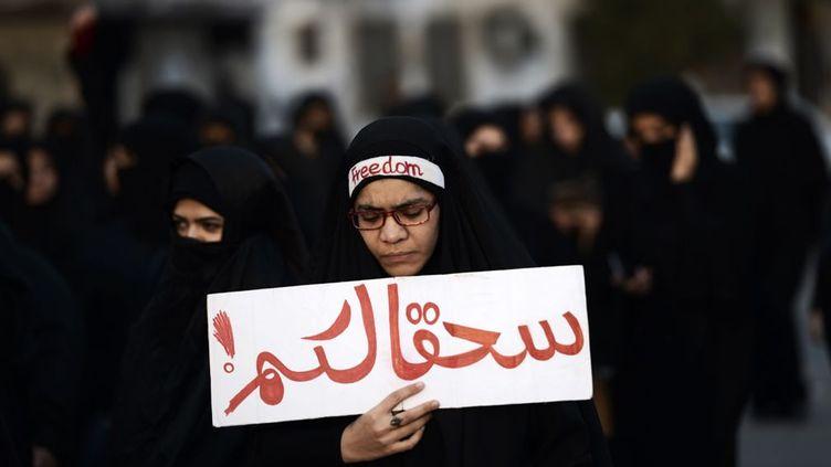 A Bahreïn, une femme manifeste dans le village de Jidhafs, à l'ouest de Manama, la capitale, contre l'exécution de l'important dignitaire religieux chiite Nimr al-Nimr par les autorités saoudiennes , le 2 Janvier 2016. Bahreïn compte une majorité de chiites comme la région d'Arabie saoudite, riche en pétrole, où le religieux exécuté a été un moteur dans les manifestations qui ont éclaté en 2011 pour protester contre ce que les chiites considèrent comme leur marginalisation dans le royaume. Sur le panneau on peut lire : «soyez damnés» . (MOHAMMED AL-SHAIKH / AFP)