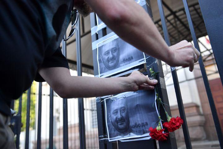 Un activiste accroche des fleurs près d'une photo d'Arkadi Babtchenko, sur la grille de l'ambassade russe à Kiev (Ukraine), le 30 mai 2018. (SERGEI SUPINSKY / AFP)