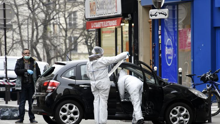 """Les experts de la police scientifique procèdent à des prélèvements, le 7 janvier 2015, sur la voiture abandonnée par les tueurs de """"Charlie Hebdo"""". (DOMINIQUE FAGET / AFP)"""