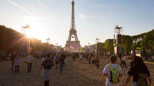 Des spectacteurs au pied de la tour Eiffel, à Paris, lors la demi-finale de l'Euro 2016, le 6 juillet 2016. (GEOFFROY VAN DER HASSELT / AFP)