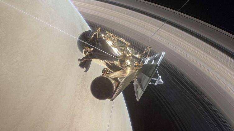 Vue d'artiste illustrant la sonde Cassini entre Saturne et ses anneaux. (SIPA)
