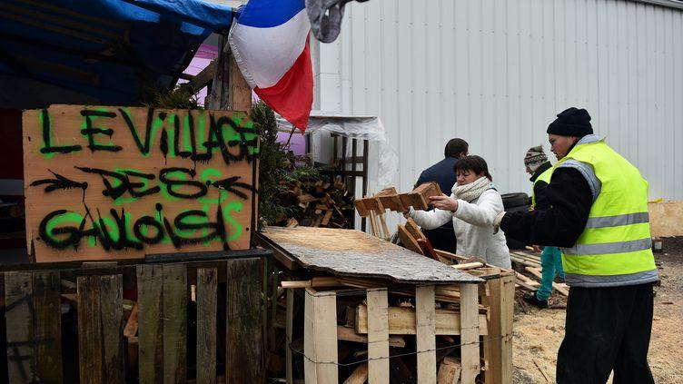 """Des """"gilets jaunes"""" installés sur le rond-point de Sablé-sur-Sarthe (Sarthe), le 16décembre2018. (JEAN-FRANCOIS MONIER / AFP)"""