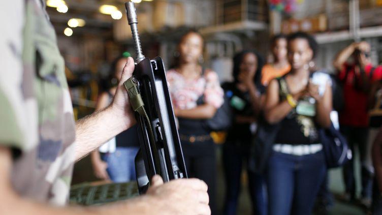 Un soldat de la Marine présente un fusil d'assaut, à des jeunes lors de la Journée d'appel de préparation à la défense, le 17 mars 2010, à Fort-de-France. (PATRICE COPPEE / AFP)