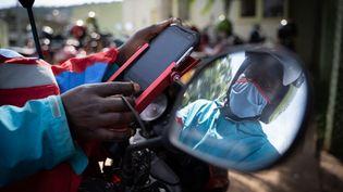 Un conducteur de moto-taxi à Kigali (Rwanda) vérifie son téléphone mobile. Depuis mars 2020, le gouvernement impose le règlement des courses via une application de paiment mobile. (SIMON WOHLFAHRT / AFP)